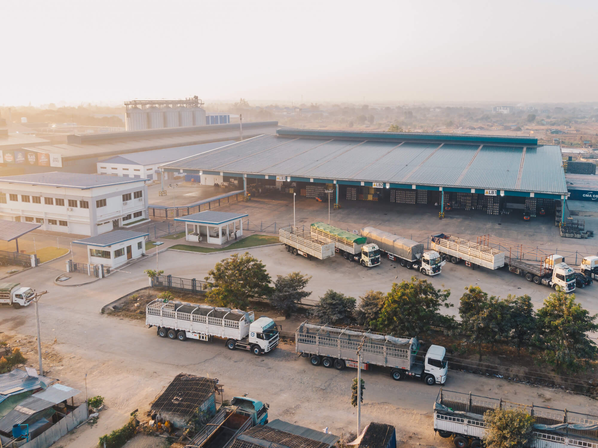 aerial-view-of-factory-trucks-parked-near-the-warehouse-at-daytime (1)